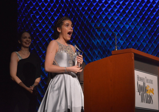 girl looking shocked yet excited after recieving an award on stage while wearing a beautiful silver gown